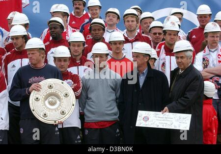 (dpa) - The players of the German Bundesliga champion FC Bayern Munich all wear hardhats while they pose with their - Stock Photo