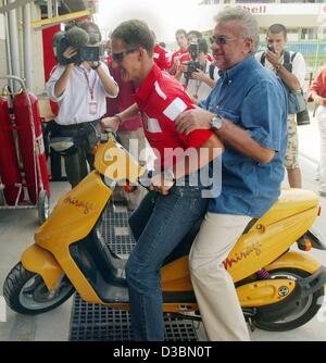 (dpa) - German formula one champion Michael Schumacher (front) arrives with his manager Willi Weber on a motor-scooter - Stock Photo