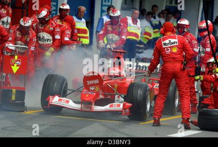 (dpa) - Ferrari mechanics put out the fire on a filler plug as German formula one champion stops in the pit lane - Stock Photo