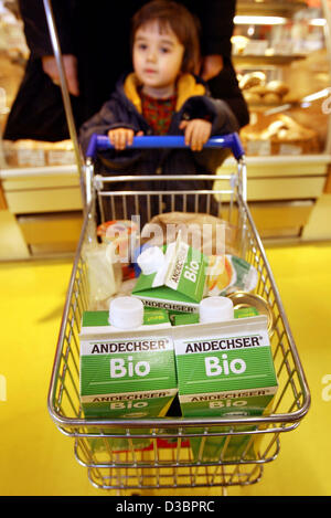 (dpa files) - A small child helps his mother push the shopping cart at the organic supermarket 'Basic' in Frankfurt, - Stock Photo