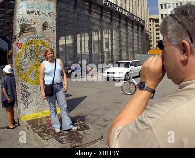 (dpa) - A tourist takes a photo of his daughter posing in front of a remnant of the Berlin Wall on Potsdamer Platz - Stock Photo
