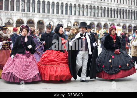 Ladies and Gentlemen Heading to the Masked Ball in St Marks Square Venice - Stock Photo