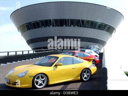 (dpa) - A yellow Porsche Carrera GT stands in front of the Porsche factory in Leipzig, Germany, 28 August 2003. - Stock Photo