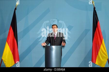 (dpa) - German Chancellor Gerhard Schroeder stands between two national flags as he speaks during a press conference - Stock Photo
