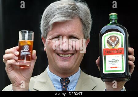 (dpa) - Hasso Kaempfe, Chairman of the Mast Jaegermeister AG, presents a bottle and a glass of Jaegermeister cordial - Stock Photo