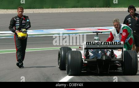 (dpa) - Danish formula one pilot Niclas Kiesa of Minardi (L) walks back to the pits after dropping out during the - Stock Photo