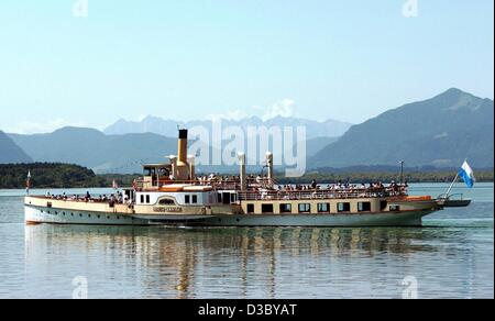 (dpa) - In front of a panorama of the Tyrolean Alps the paddle steamer 'Ludwig Fessler' steers across Lake Chiemsee - Stock Photo