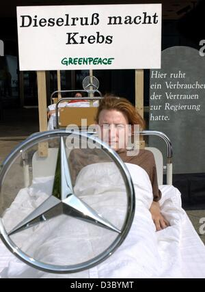 (dpa) - A Greenpeace activist protesting against pollution from diesel engines lies in a hospital bed in front of - Stock Photo