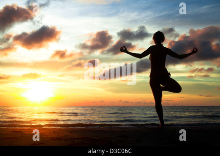 Young woman practicing yoga on the beach during the sunset - Stock Photo