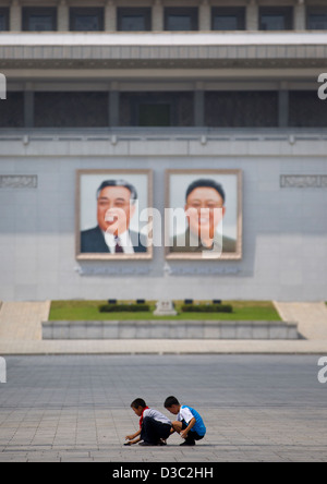 Kids Playing In Front Of Kim Il Sung And Kim Jong Il Giant Portraits On Kim Il Sung Square, Pyongyang, North Korea - Stock Photo
