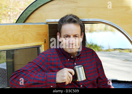 man drinking coffee at campsite - Stock Photo