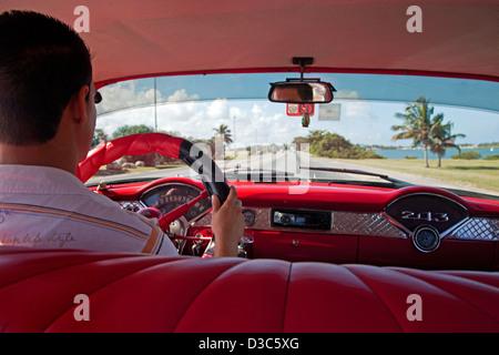 Cuban taxi driver and interior of old 1950s vintage American car / Yank tank driving at Varadero, Matanzas, Cuba, - Stock Photo