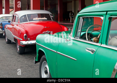 Old 1950s vintage American cars / Yank tank used as taxis waiting in front of the Varadero airport, Matanzas, Cuba, - Stock Photo