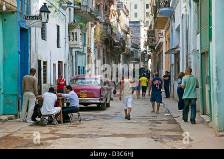 Busy street scene and red old 1950s vintage American car / Yank tank in Old Havana / La Habana Vieja, Cuba, Caribbean - Stock Photo