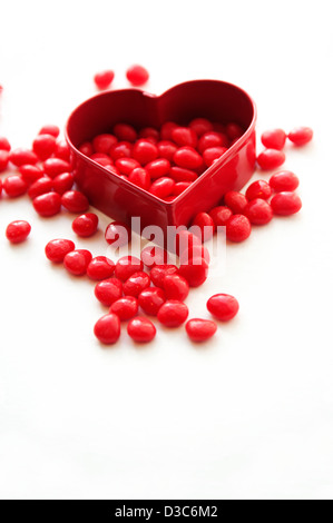 Red candy cinnamon hearts and heart shape cookie cutter - Stock Photo