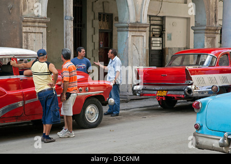 Cuban men discussing on street and red old 1950s vintage American cars / Yank tank in Old Havana / La Habana Vieja, - Stock Photo
