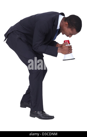 Man in suit shouting into megaphone - Stock Photo