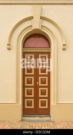 Immaculate brown and cream painted arched double wooden doors with decorative rectangular panels in cream wall of - Stock Photo