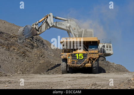 Excavator loading soil into tip truck at open cut coal mine in central Queensland, Australia - Stock Photo