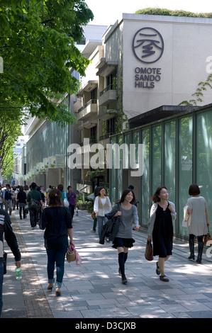 Shoppers strolling past Omotesando Hills shopping mall along Omotesando-dori Street in the upscale Shibuya ward - Stock Photo