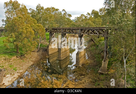 Historic wooden trestle railway bridge through woodland and reflected in calm water of narrow stream far below at - Stock Photo