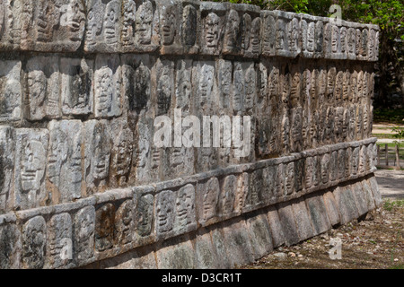 Detail of skull carvings on the wall of skulls (Tzompantli), Chichen Itza, Mexico - Stock Photo