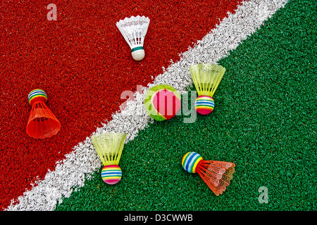 Badminton colored shuttlecocks and tennis ball, placed on synthetic field. - Stock Photo