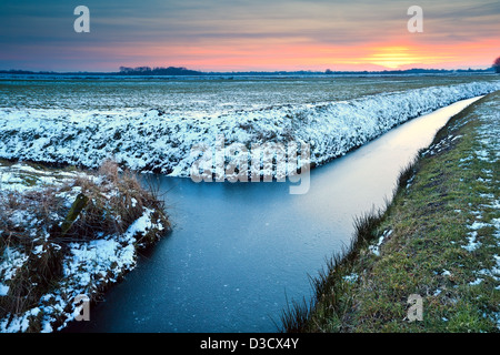 sunset over winter meadows and frozen canals in Netherlands - Stock Photo