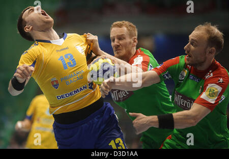 Bacau's Cristian Githa (L-R) is held by Stefan Kneer and Yves Grafenhorst of SC Magdeburg during the Handball European - Stock Photo