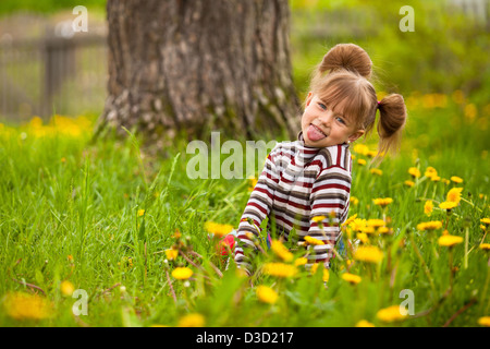 Little lovely girl playing in the park, shows the language (looking at the camera) - Stock Photo