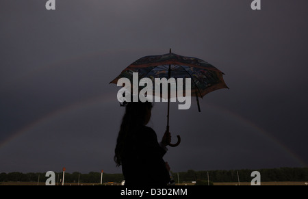 Hoppegarten, Germany, Silhouette, woman with umbrella standing in front of a rainbow - Stock Photo