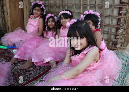 Dubai, United Arab Emirates, girls in pink dresses sitting on the floor - Stock Photo