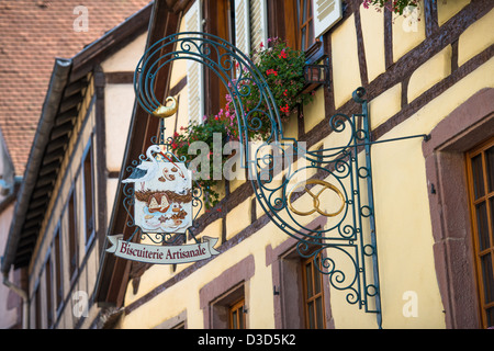 Inn sign of Biscuitere Artisanale in Kaysersberg, along the Wine Route, Alsace Haut-Rhin France - Stock Photo