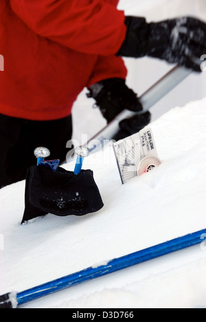 Slope measuring gauge and other devices in use by a skier digging an avalanche test, Wallowa Mountains, Oregon. - Stock Photo
