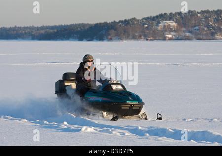 Dill, Sweden, a snowmobile rider crosses the Baltic bay Stora Värtan - Stock Photo