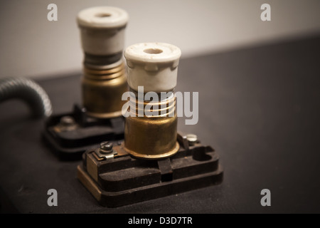Two vintage electrical fuses on dark panel - Stock Photo