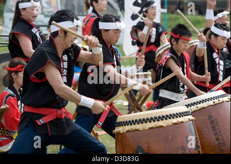 A team of energetic drummers young and old beat a musical rhythm on odaiko Japanese drums with wooden mallets at - Stock Photo