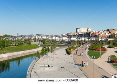 People walking along Madrid Rio park on the banks of the Manzanares river, Madrid, Spain - Stock Photo