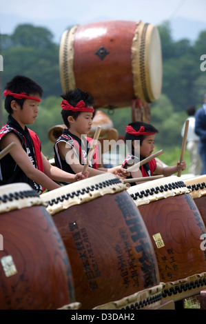 A team of serious young drummers beat a musical rhythm on odaiko Japanese drums with wooden mallets at a festival. - Stock Photo