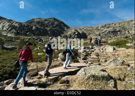 Young people hiking in the Penalara Nature Reserve on the Sierra de Guadarrama, Madrid, Spain - Stock Photo
