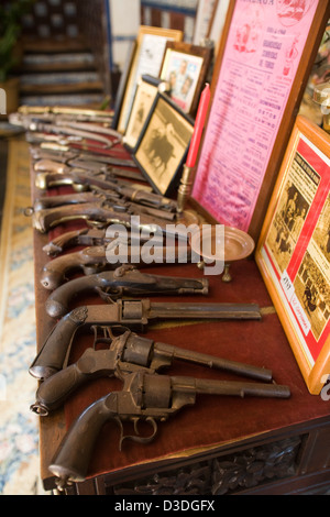 LA RUIZA FINCA, HUELVA, SPAIN, 21st FEBRUAY 2008: A collection of antique guns lie on a table beside bullfighting - Stock Photo