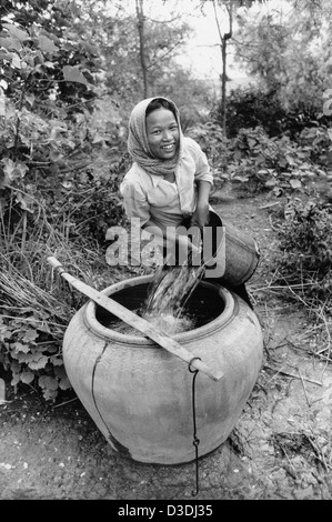 Prey Veng province, Cambodia:  A young woman fills the household's water jar with water from a well. - Stock Photo