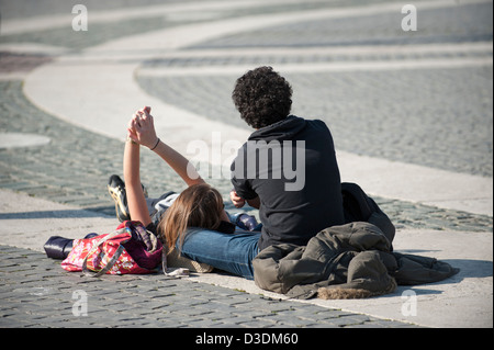 Couple lying in St Peter's Square. - Stock Photo