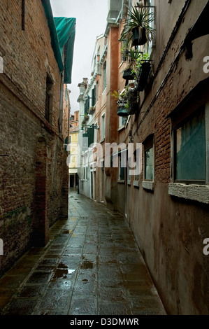 Back street in Venice, Italy, wet after rain. - Stock Photo