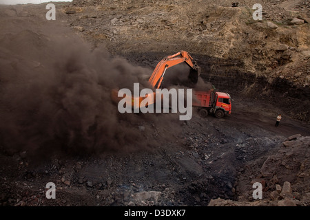WUDA COAL FIELD, WU HAI, INNER MONGOLIA, CHINA - AUGUST 2007: A front shovel excavator fills a 50 ton truck with - Stock Photo