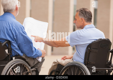 Design engineers reading Plans, one with muscular dystrophy and one with a spinal cord injury - Stock Photo