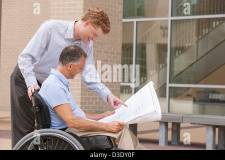 Design engineers reading Plans, one with a spinal cord injury - Stock Photo