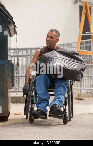 Loading dock worker with spinal cord injury in a wheelchair putting a bag in the dumpster - Stock Photo
