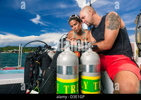 Two scuba divers review dive plan and check technical equipment on boat before starting tec dive. Roatan, Honduras - Stock Photo