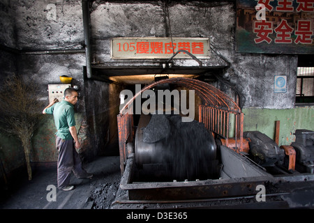 XIMING COAL MINE, TAIYUAN, CHINA - AUGUST 2007: A conveyor belt operator monitors coal on its way from the mine - Stock Photo
